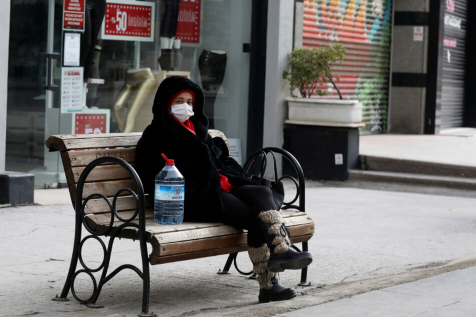Ankara: Eine Frau sitzt mit Mund-Nasen-Schutz an einer Straße auf einer Bank.