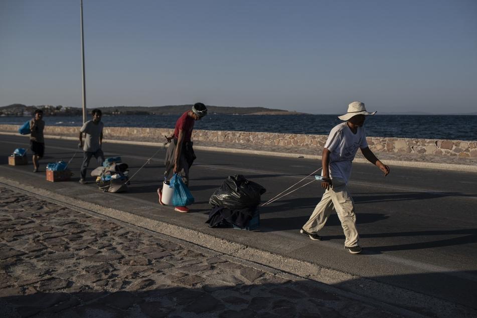 Migranten ziehen ihre Habseligkeiten mit sich und gehen entlang einer Straße in der Nähe der Stadt Mytilene auf der nordöstlichen Seite der Insel Lesbos.