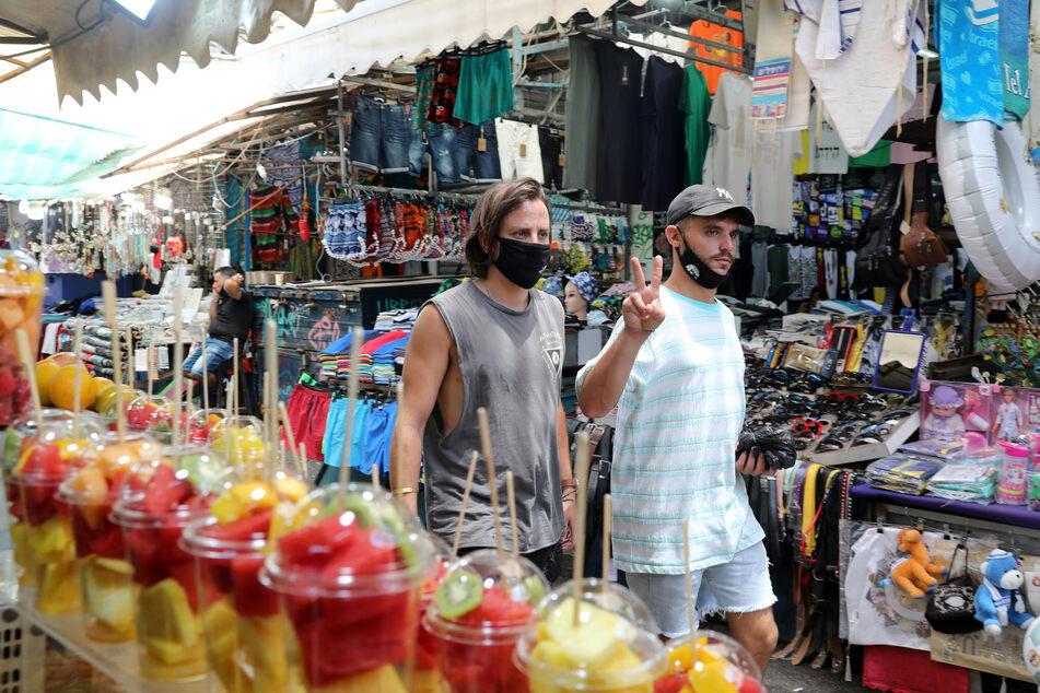 14. Juli, Tel Aviv: Nur einer von zwei Männern trägt beim Besuch eines Marktes den Mundschutz korrekt. Nach einem starken Anstieg der Corona-Infektionen hält Israels Gesundheitsminister einen weiteren Lockdown in dem Land für kaum noch vermeidbar.