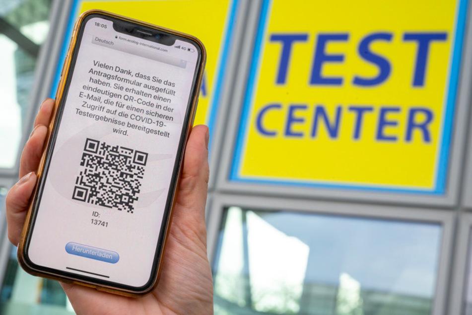Eine Frau hält ihr Smartphone in die Kamera, mit dem sie sich zuvor am Münchner Flughafen für den Corona-Test angemeldet hat.