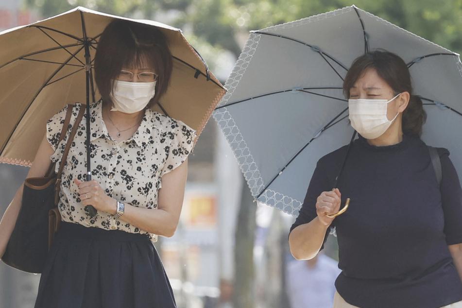 Menschen laufen mit Mundschutz und Sonnenschirmen unter der starken Sonne.