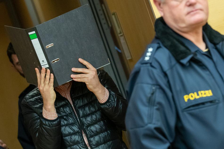 Der wegen Missbrauchs von Kindern angeklagte Logopäde trifft zum Prozessbeginn im Sitzungssaal im Landgericht ein und hält sich einen Aktenordner vor das Gesicht.