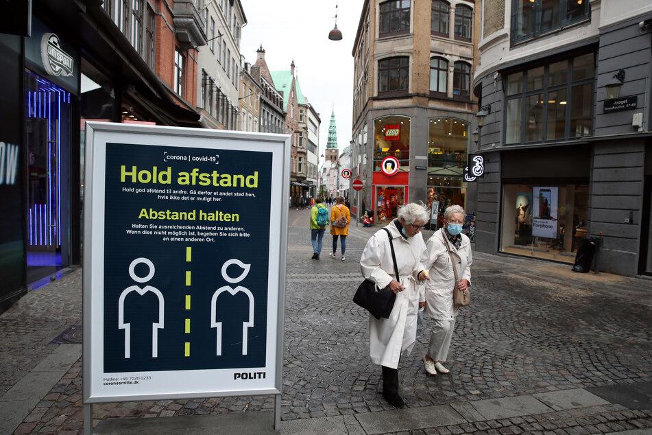 """""""Abstand halten"""" steht auf einem Schild in einer Straße in Kopenhagen."""