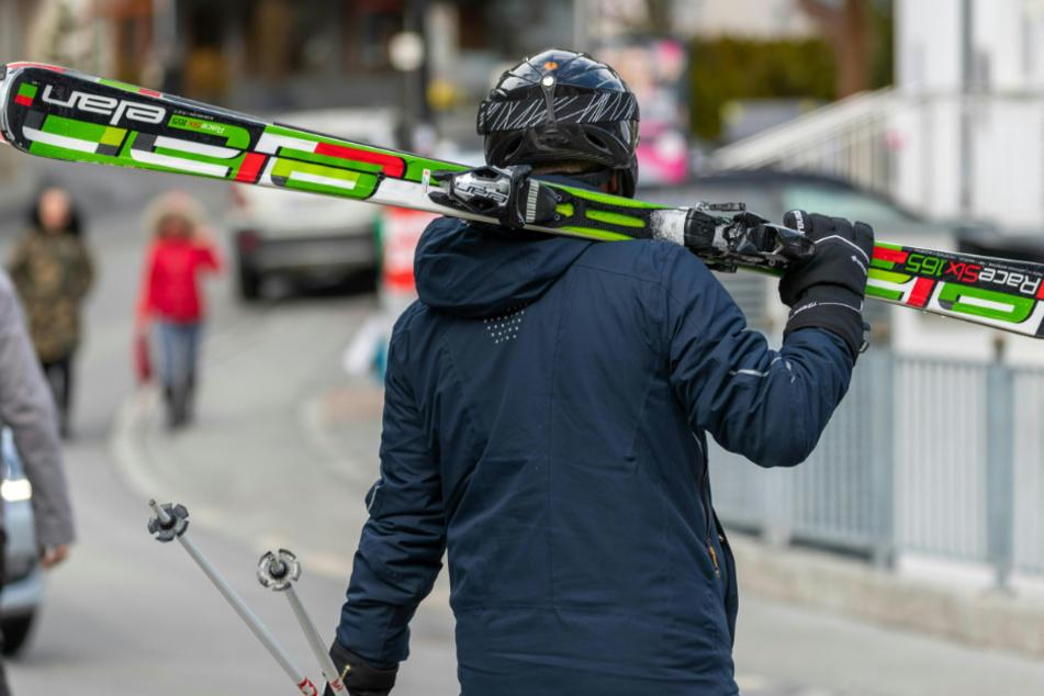Ein Skifahrer geht mit geschulterten Skiern auf einer Straße.