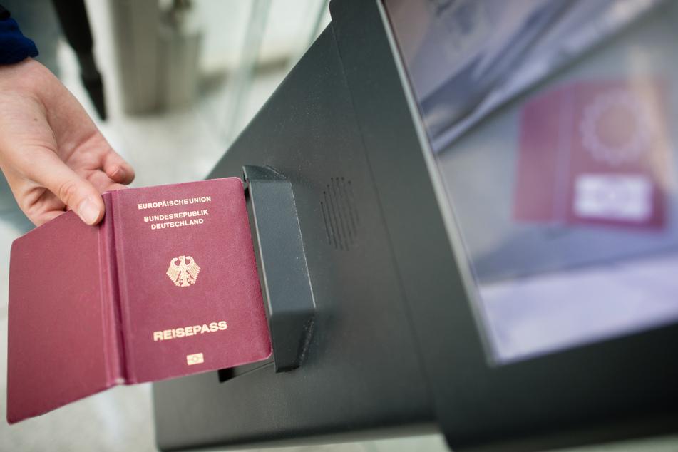 Eine Frau hält einen Reisepass an das Lesegerät eines EasyPass-Systems zur teilautomatisierten Grenzkontrolle am Flughafen in München.