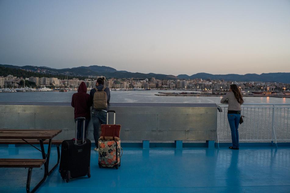 Drei Fahrgäste beobachten am 25.06.2020 die Skyline der Stadt Barcelona während der ersten Wochenend-Bootsfahrt von Barcelona nach Mallorca nach dem Ende des Alarmzustandes in Spanien.