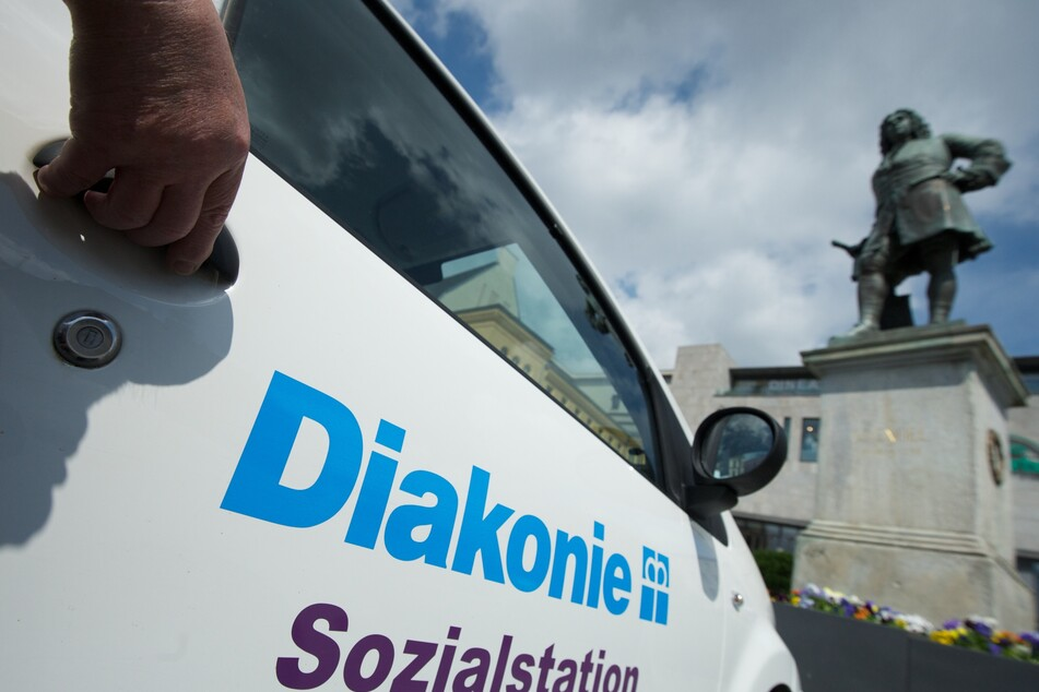 Eine Hand öffnet ein Fahrzeug der Diakonie.