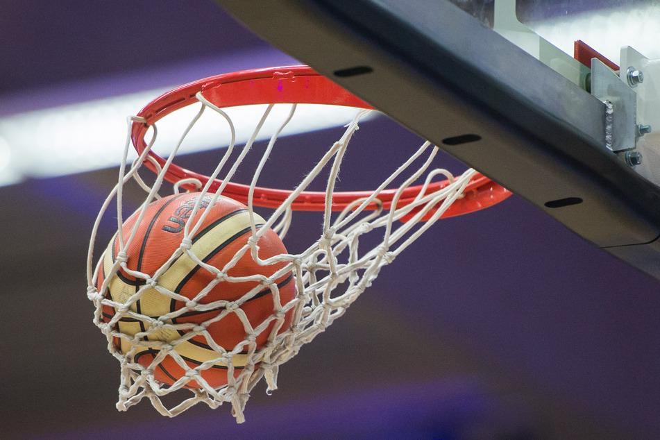 Ein Basketball fliegt in einen Korb.