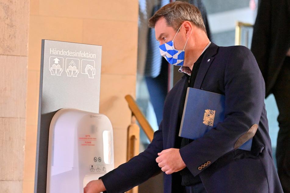 Markus Söder (53, CSU), Ministerpräsident von Bayern, trägt zu Beginn der Kabinettssitzung in der Bayerischen Staatskanzlei eine Maske, während er sich Hände an einem Spender desinfiziert.