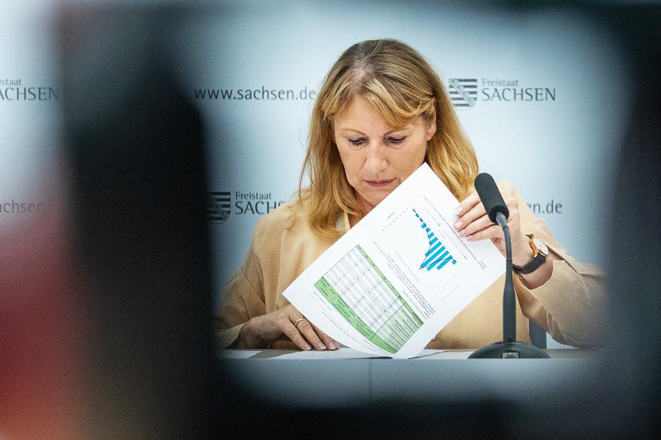 Sozialministerin Petra Köpping (SPD) schaut in ihre Unterlagen mit den aktuellen Fallzahlen. (Archivbild)