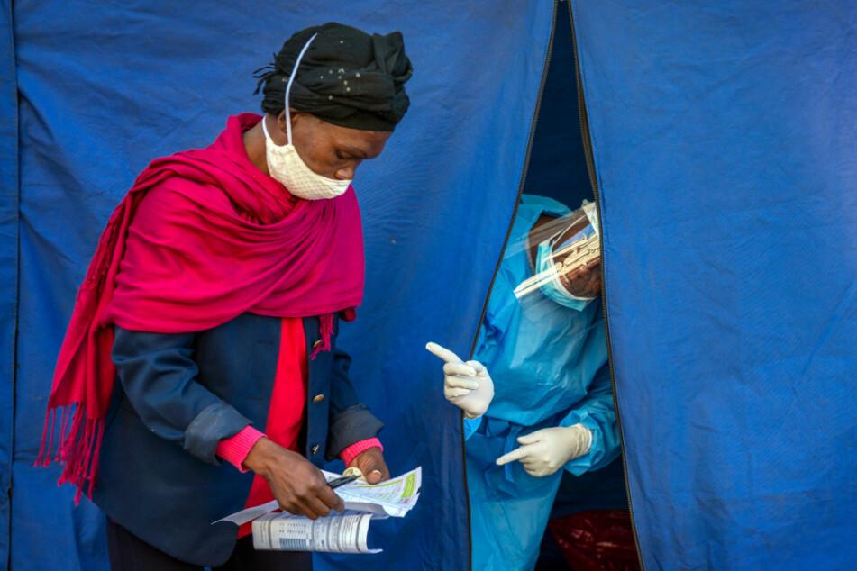 Mitarbeiter der Gesundheitsbehörde prüfen eine Liste mit Personen, die sowohl auf Covid-19, als auch auf HIV und Tuberkulose getestet werden sollen.