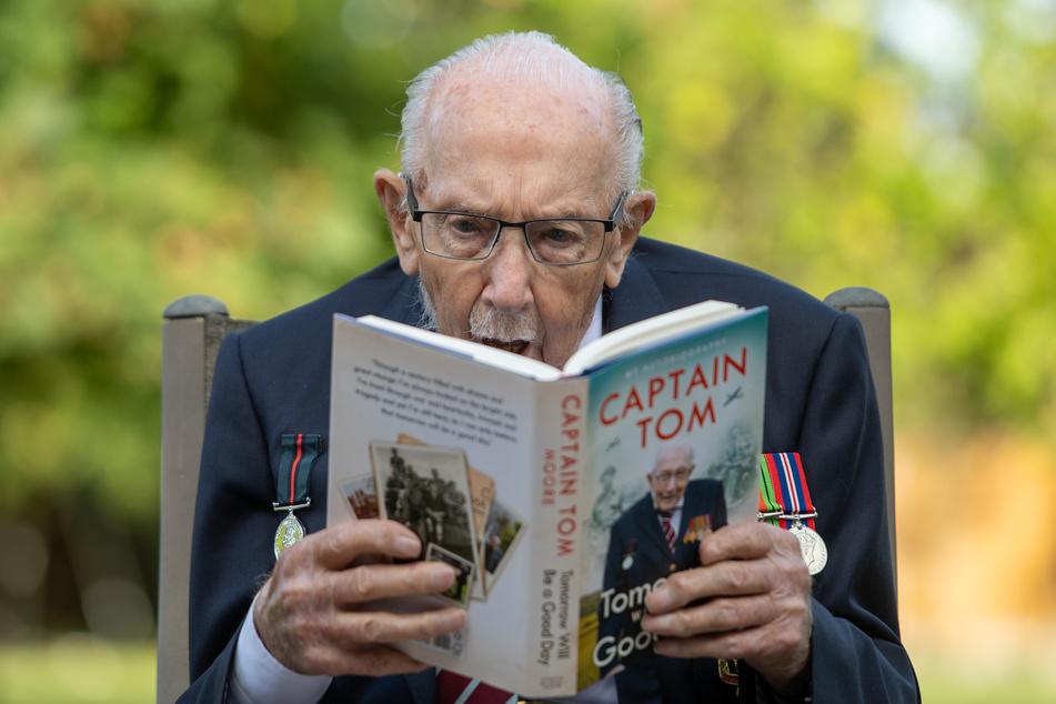 """Captain Sir Tom Moore hält in seinem Haus in Marston Moretaine, Bedfordshire, am Tag der Veröffentlichung seiner Autobiographie """"Tomorrow Will Be A Good Day"""" ein Exemplar des Buchs."""