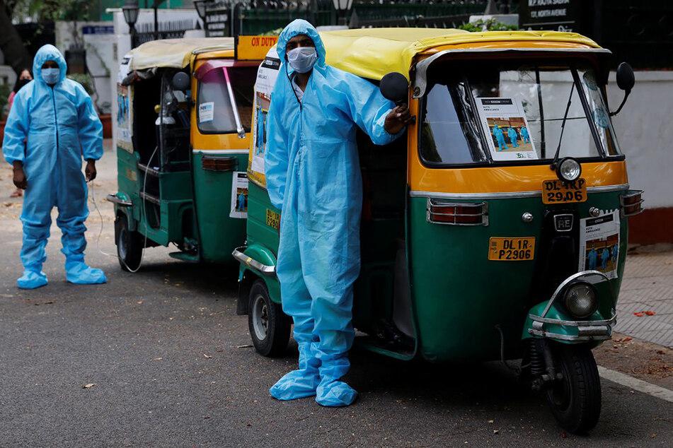 Indien, Neu Delhi: In Schutzanzügen und mit Mund-Nasenschutz stehen Fahrer vor Rikscha-Krankenwagen, mit denen sie Corona-Patienten gratis durch die Hauptstadt Neu Delhi bringen.