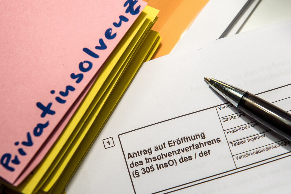 """Das Wort """"Privatinsolvenz"""" steht auf einem Trennblatt, während davor ein Antrag zur Eröfnung eines Insolvenzverfahrens liegt."""