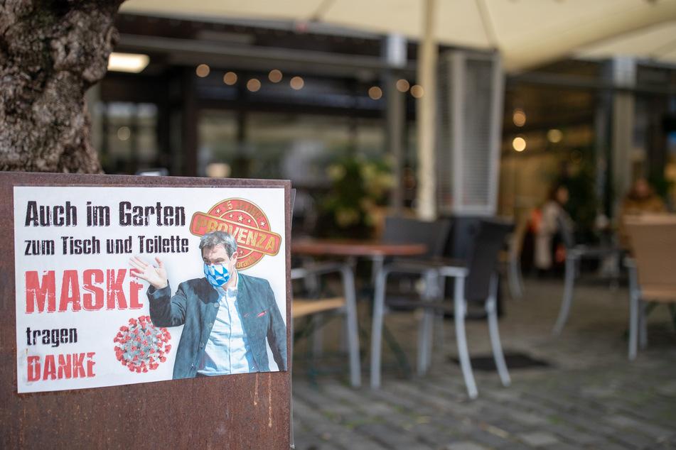 """Ein Schild mit der Aufschrift """"Auch im Garten, zum Tisch und Toilette Maske tragen - Danke"""" und dem Konterfei des bayerischen Ministerpräsidenten mit Maske hängt am Eingang zum Außenbereich eines Restaurants."""