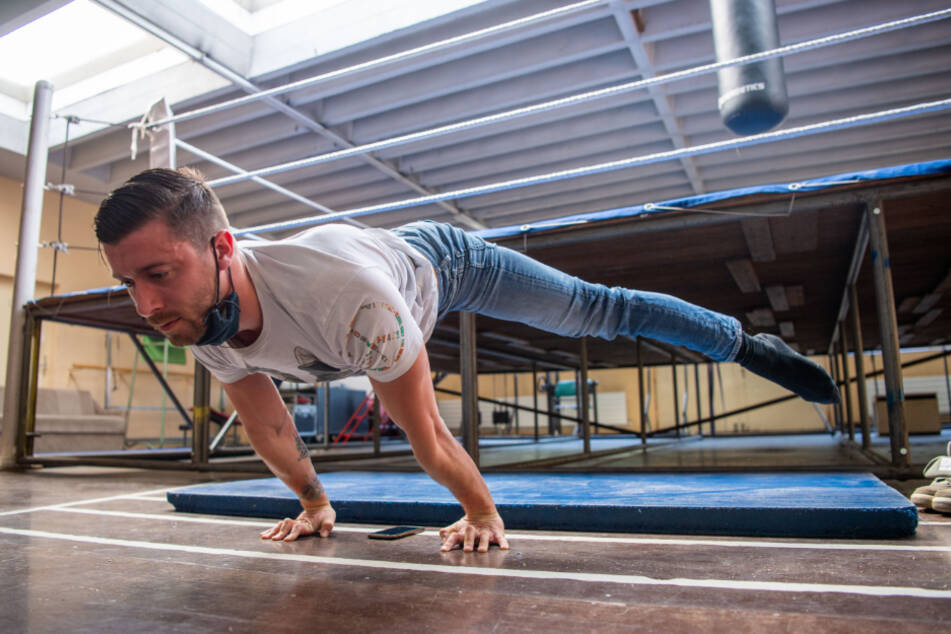 Sven Jahn-Munos, Strapatenartist, macht Streckübungen im Sportraum des Zirkus.