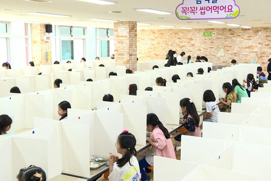 """Schülerinnen und Schüler essen in der Cafeteria der Grundschule """"Daejeon Seonyucho Elementary School"""" in Daejeon, 164 Kilometer südlich von Seoul, zu Mittag, wobei Trennwände an den Tischen die Kinder voneinander trennen, um sie vor einer Ansteckung mit Covid-19 zu schützen."""