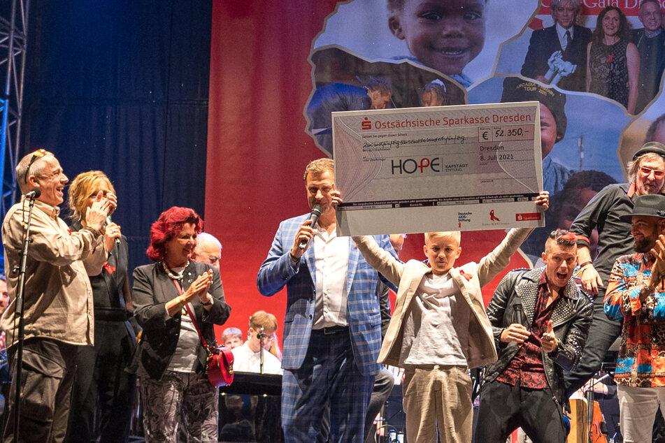 Phil Schaller (15) zeigt zum Finale den Spendenscheck - die Summe wurde nach dem Konzert von einem anonymen Spender aufgerundet.