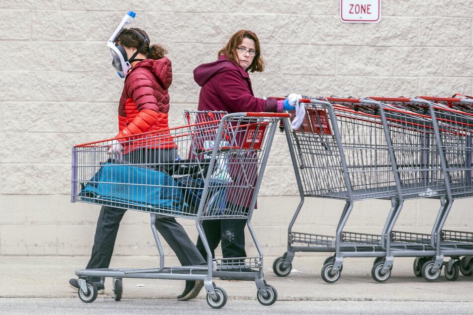 Eine Mitarbeiterin eines Supermarkts Costco desinfiziert Einkaufswagen, während sie auf eine Kundin reagiert, die eine Schnorchelmaske trägt.