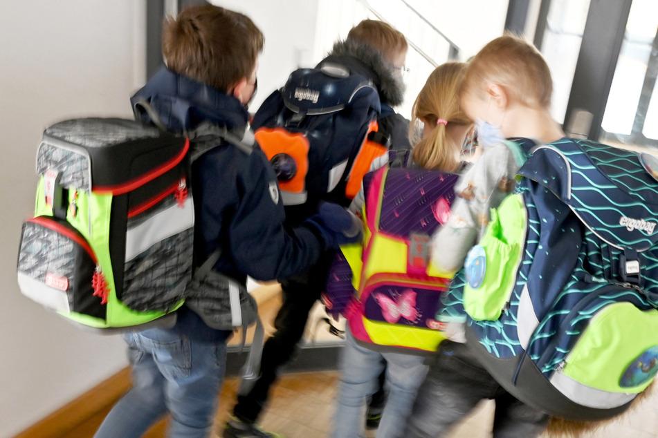 Kinder rennen nach dem Unterricht über den Flur einer Grundschule.
