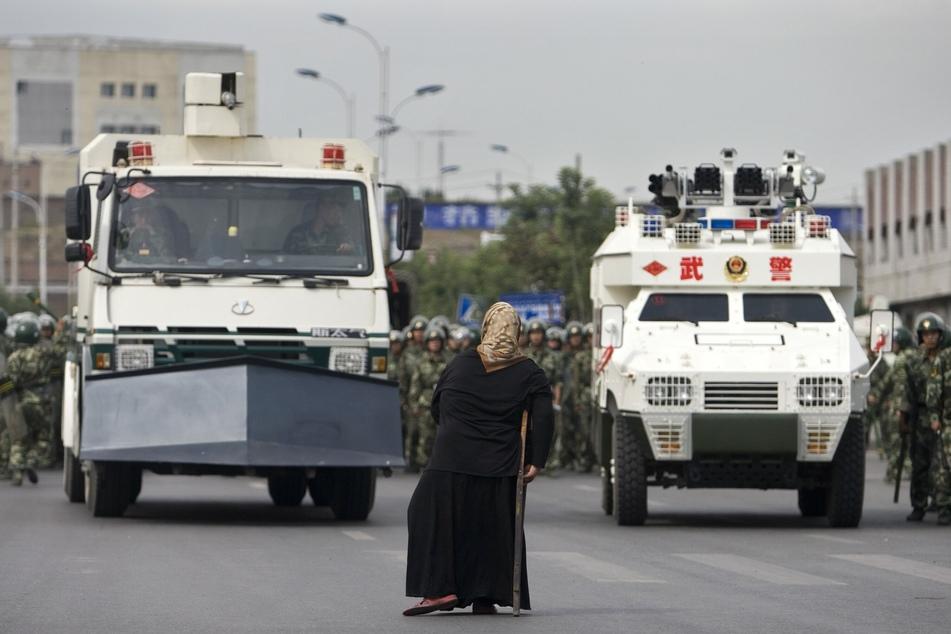 Eine uigurische Frau steht vor gepanzerten Fahrzeugen während einer Demonstration.