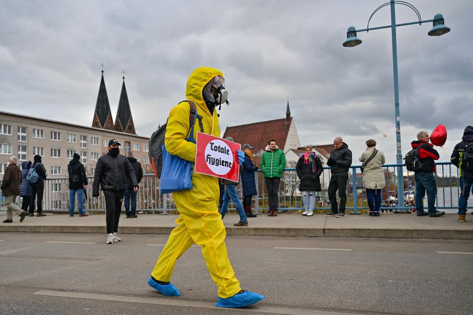 """Ein Teilnehmer einer Demonstration gegen Corona-Maßnahmen trägt einen gelben Schutzanzug und ein Schild mit der Aufschrift """"Totale Hygiene"""" und geht über den Grenzübergang Stadtbrücke ins polnische Slubice."""