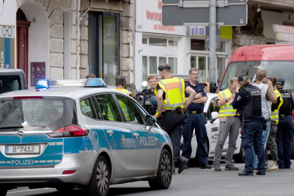 Polizisten und Feuerwehrleute stehen vor einer Bank im Stadtteil Wilmersdorf.