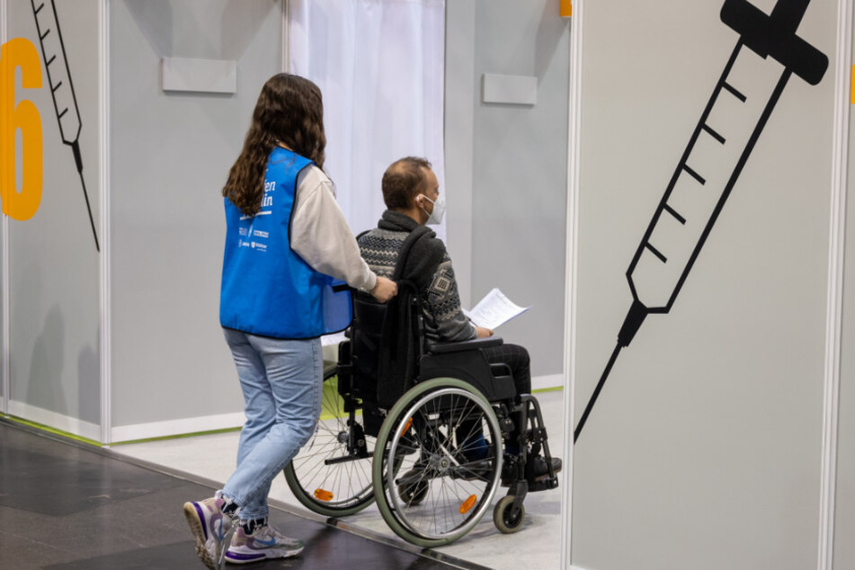 Im Impfzentrum im Velodrom schiebt eine Helferin bei einem Probelauf einen Statisten im Rollstuhl durch einen Gang.