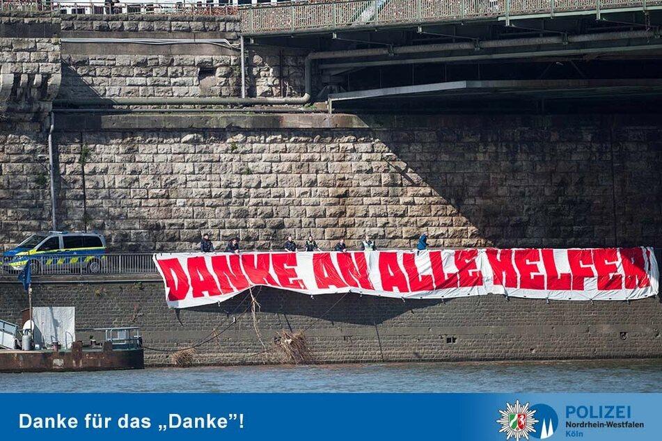 Das Danke-Banner hängt nun an der Rheinpromenade unterhalb der Hohenzollernbrücke in Köln.