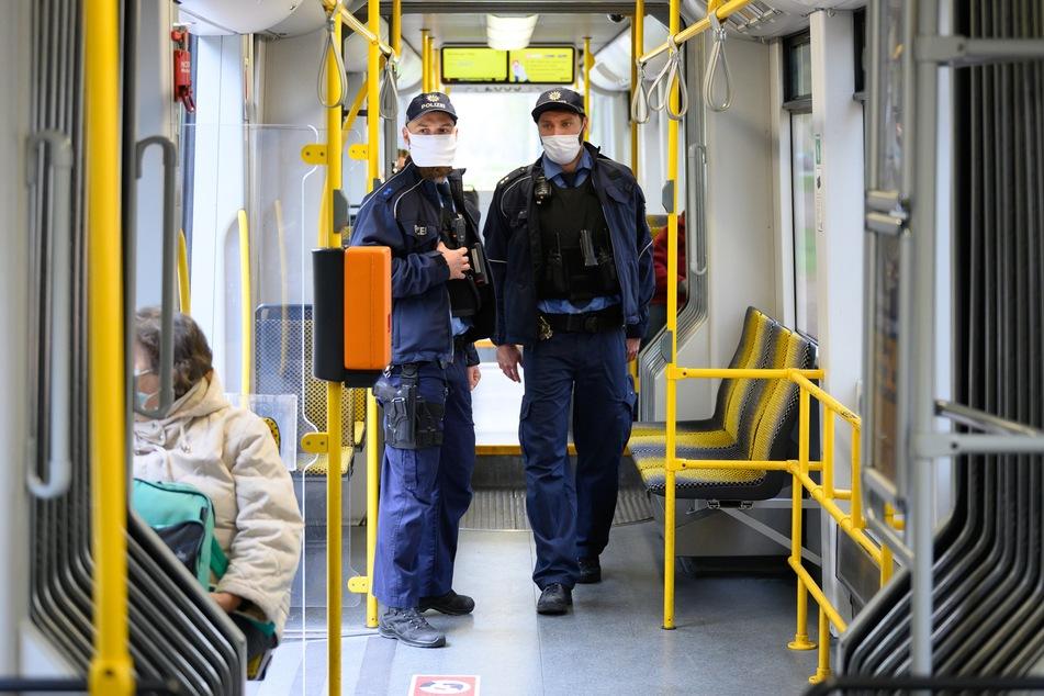 Gabor Schulz (l), Polizeimeister, und Andre Richter, Polizeioberkommissar, stehen anlässlich einer Kontrolle der Einhaltung der Maskenpflicht im öffentlichen Personennahverkehr in einer Straßenbahn.