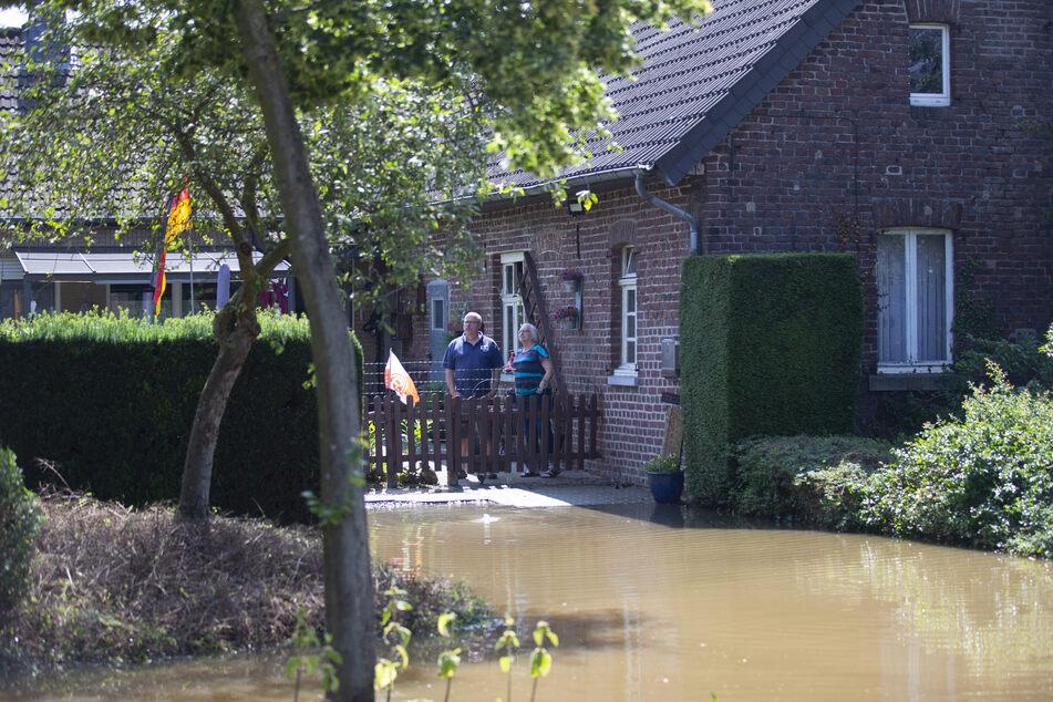 Bewohner schauen auf das Hochwasser vor ihrem Haus: Die Vorwarnung für eine Evakuierung in den Orten Effeld und Steinkirchen wurde aufgehoben.