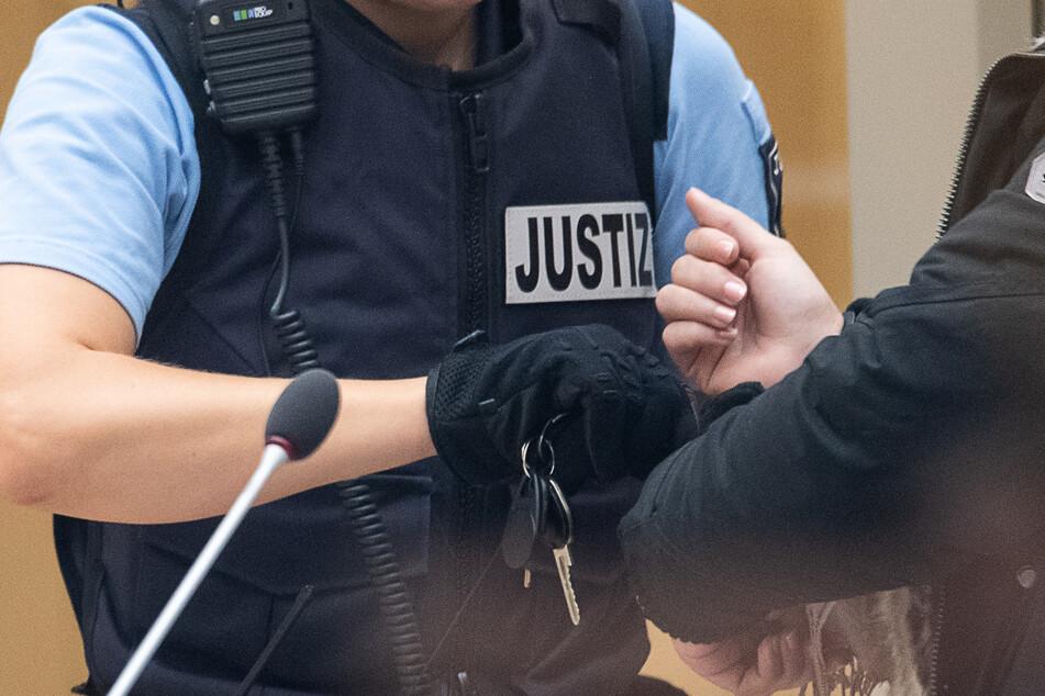 Eine Justizbeamtin schließt während des Beginns eines Prozesses gegen eine IS-Rückkehrerin die Handschellen auf. (Archivbild).