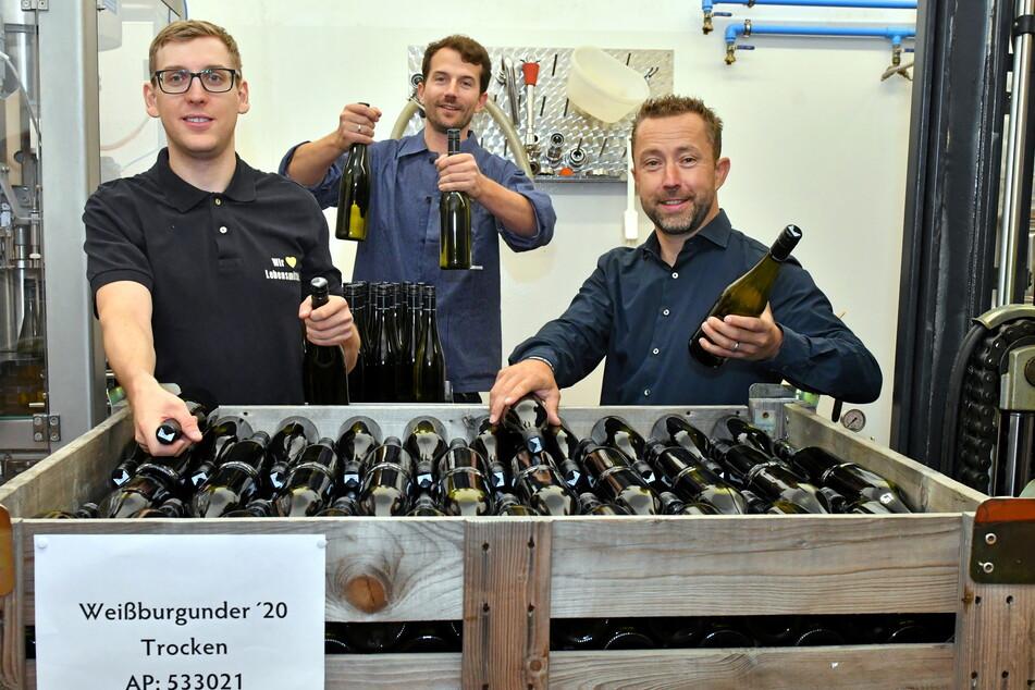 Azubi Kevin Grune (27, v. l.n.r.) stapelt mit Edeka-Chef John Scheller (43) und Kellermeister Jacob Wiedemann (38) den Weißburgunder zur Lagerung in Kisten.