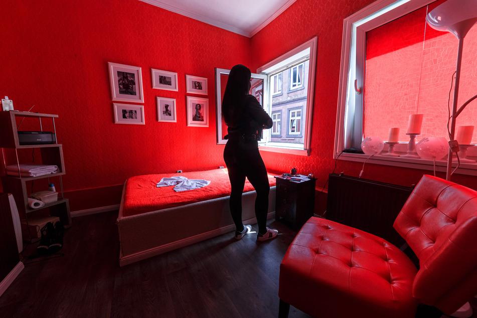 Eine Prostituierte steht in einem Bordell in der Herbertstraße am Fenster ihres Arbeitszimmers.