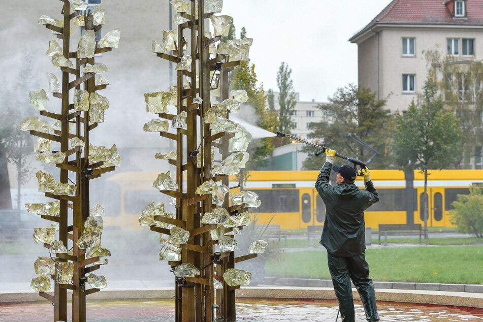 Brunnenbetreuer Uwe Möller (54) reinigt den Glasbrunnen in der Lingnerstadt.