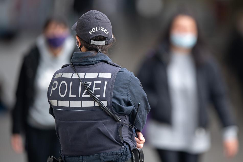 Eine Polizistin überprüft die Maskenpflicht.