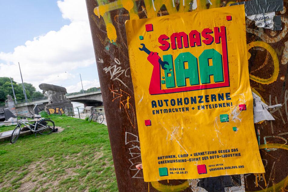"""Ein gelbes Plakat mit der Aufschrift """"Smash IAA Autokonzerne entmachten und enteignen!"""" klebt an einer Wand in der Stadt."""