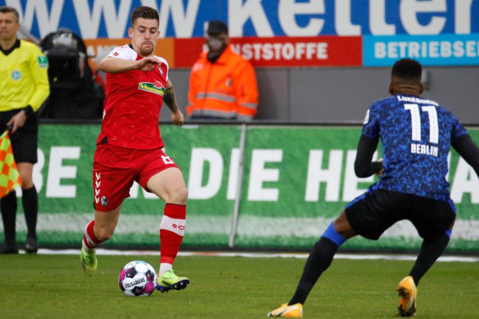 Baptiste Santamaria (l.) vom SC Freiburg im Zweikampf mit Herthas Dodi Lukebakio.