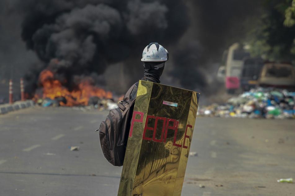 """Ein Demonstrant hält ein behelfsmäßiges Schutzschild mit der Aufschrift """"People"""" und sieht in Richtung brennender Trümmer einer Straßenblockade."""