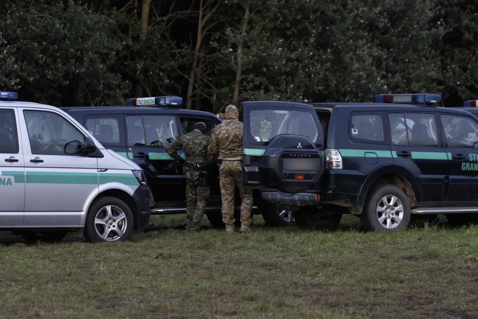 Polizeibeamte stehen an der polnischen Grenze, an der sich mehrere Dutzend Flüchtlinge befinden. Ein fünf Jahre altes Kind ist dort in einem Auffanglager durch einen giftigen Pilz ums Leben gekommen.