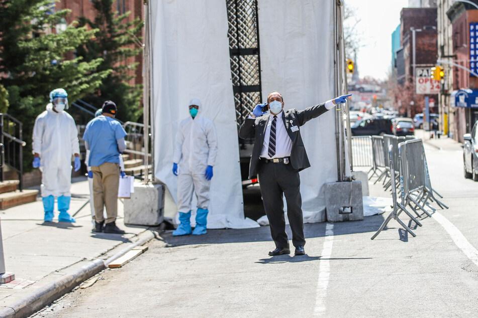 Ein telefonierender Mitarbeiter des Brooklyn Hospital Center gestikuliert während im Hintergrund medizinisches Personal in Schutzkleidung vor einen verhüllten Kühlwagen stehen, der als Leichenhalle eingesetzt werden soll.