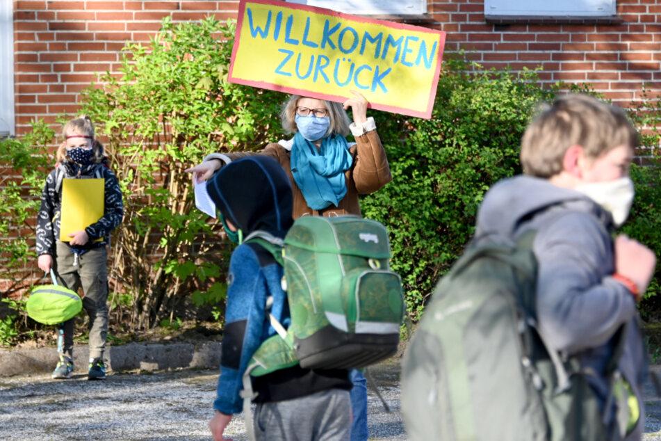 Eine Lehrerin begrüßt die an die Grundschule zurückkehrenden Kinder. (Archivbild)