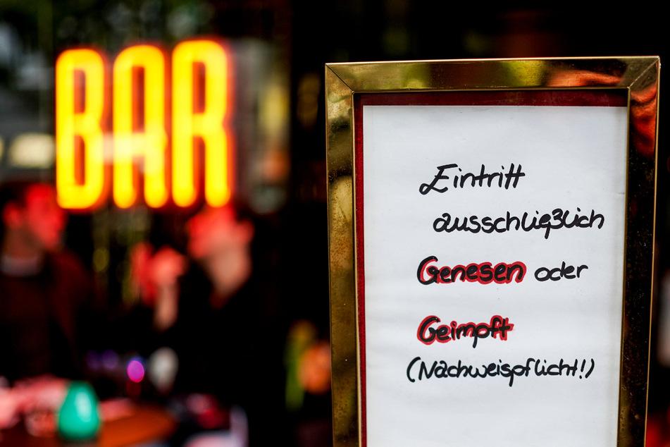 Vor einer Hamburger Bar steht ein Hinweisschild, das auf den Einlass nach der 2G-Regel hinweist. Ein Barbesitzer hat wegen dieser Regel nun eine Bombendrohung bekommen. (Symbolfoto)