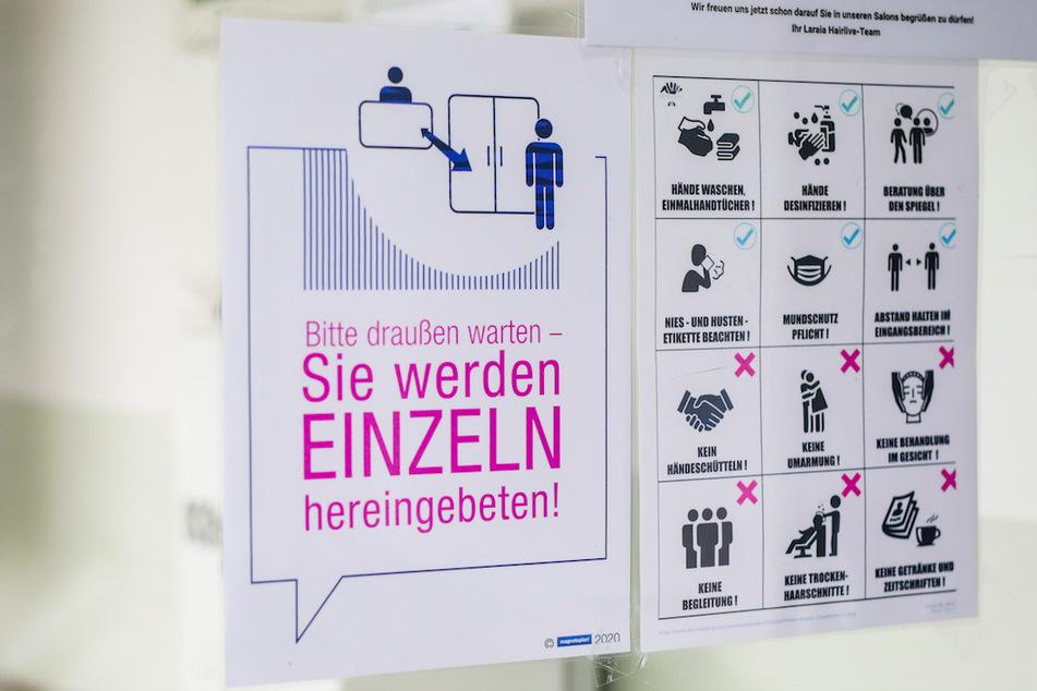 Ein Schild weist Kunden in einem Friseursalon über die neu geltenden Regeln im Salon aufgrund der Corona-Pandemie hin.