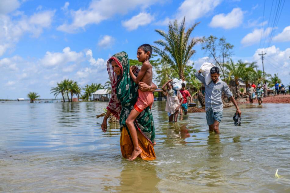 Bangladesch: Einwohner überqueren mit Kindern und Säcken auf den Armen eine überflutete Straße, nachdem viele Dörfer im Distrikt Satkhira von der Flutwelle des Zyklons Amphan überflutet wurden.
