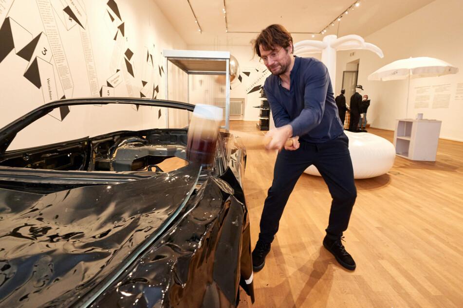 """Ist das Kunst oder muss da noch eine Beule rein? Friedrich von Borries, Kurator und Initiator der Ausstellung """"Schule der Folgenlosigkeit"""" im Museum für Kunst und Gewerbe Hamburg (MK&G), schlägt mit einem Hammer auf einen Porsche ein."""