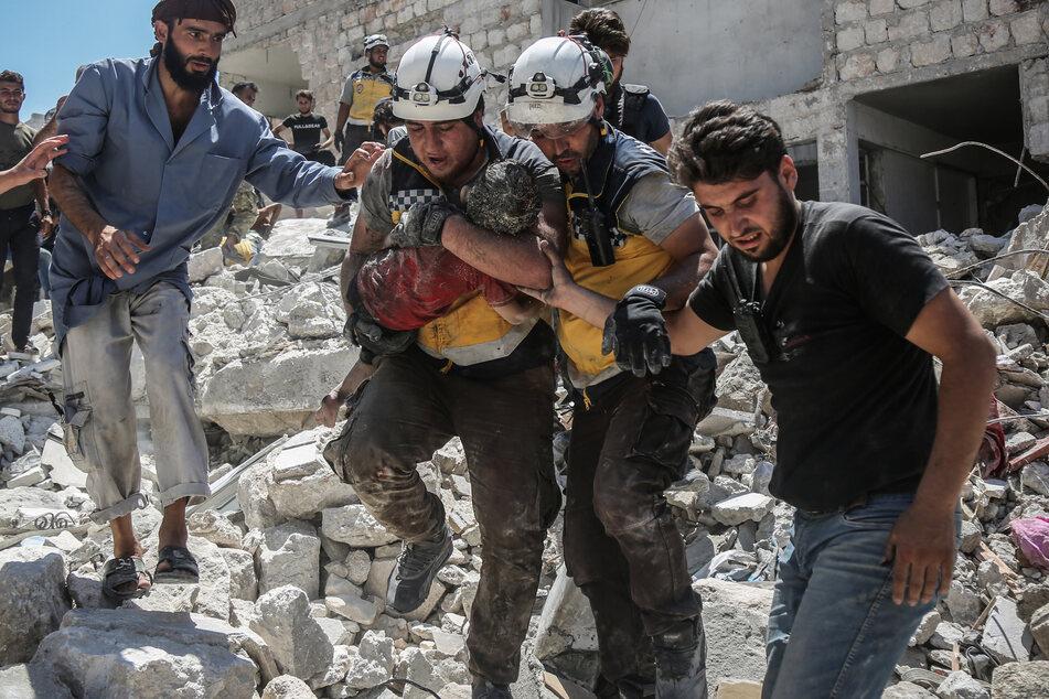 Weißhelme des syrischen Zivilschutzes tragen ein verletztes Kind aus den Trümmern eines zerstörten Gebäudes.