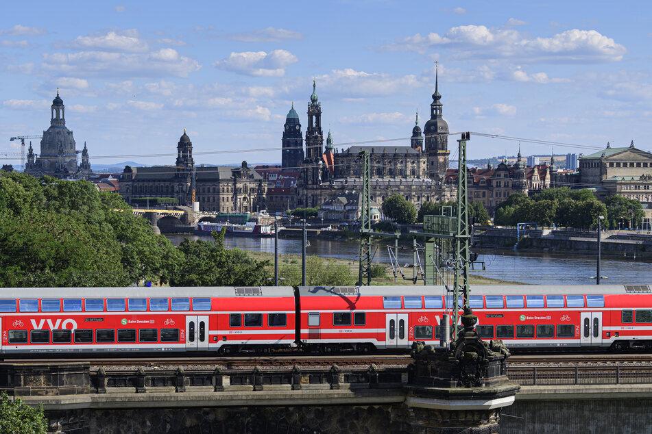 Eine S-Bahn fährt vor der historischen Altstadtkulisse auf der Marienbrücke über die Elbe.