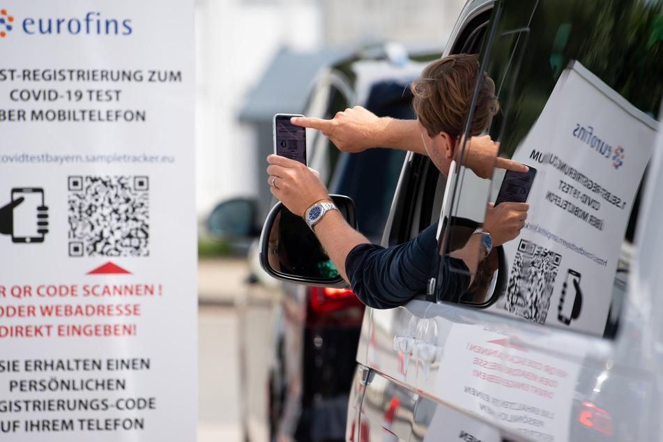 Ein Mann scannt mit seinem Smartphone an einem Corona-Testzentrum an der Autobahn 93 an der Rastanlage Inntal-Ost einen QR-Code, mit dessen Hilfe man sich für den Test anmelden kann.