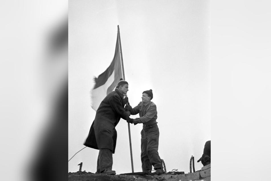 Die beiden Studenten Rene Leudesdorff (r) und Georg von Hatzfeld hissen im Dezember 1951 auf der Nordseeinsel Helgoland die Europafahne.